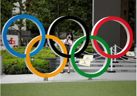 A woman wearing a protective mask amid the coronavirus disease (COVID-19) outbreak, takes a picture of the Olympic rings in front of the National Stadium in Tokyo, Japan October 14, 2020. REUTERS/Kim Kyung-Hoon
