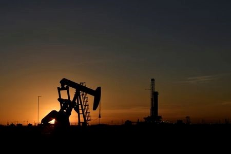 A pump jack operates in front of a drilling rig at sunset in an oil field in Midland, Texas U.S. August 22, 2018. REUTERS/Nick Oxford/File Photo