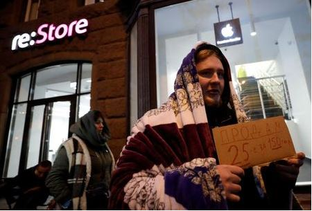 A man holds a sign about selling his place in line before the Apple's new iPhone XS and XS Max go on sale in front of a cell phone store in central Moscow, Russia September 26, 2018. REUTERS/Tatyana Makeyeva