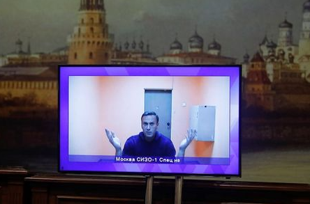 Russian opposition leader Alexei Navalny is seen on a screen via a video link during a court hearing to consider an appeal on his arrest outside Moscow, Russia January 28, 2021. REUTERS/Maxim Shemetov
