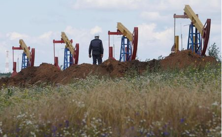 FILE PHOTO: A worker stands in front of pump jacks at the Ashalchinskoye oil field owned by Russia's oil producer Tatneft near Almetyevsk, in the Republic of Tatarstan, Russia July 27, 2017. REUTERS/Sergei Karpukhin/File Photo