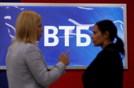 Employees pose for a picture near a board showing the logo of VTB during a tour at a branch of VTB bank in Moscow, Russia May 30, 2019. REUTERS/Evgenia Novozhenina
