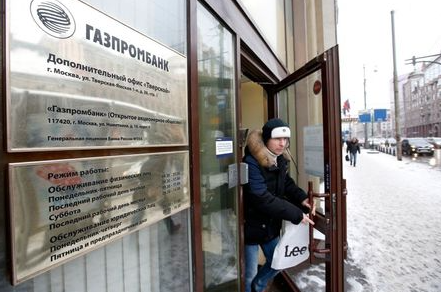 A man walks out of a branch of Gazprombank in Moscow, January 23, 2015. Russia may have to spend more than $40 billion (26.64 billion pounds) this year to avert a banking crisis, as the growing likelihood of a sharp recession threatens to pile extra costs on a sector suffering from Western sanctions over Ukraine and a plunge in the rouble. The government is soon to distribute up to 1 trillion roubles of OFZ treasury bonds issued late last year to banks including VTB, Gazprombank and Rosselkhozbank, all state-controlled and under sanctions imposed by Western countries to punish Russia for its involvement in Ukraine. REUTERS/Sergei Karpukhin (RUSSIA - Tags: BUSINESS POLITICS)