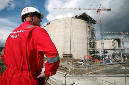 An employee of Sakhalin Energy stands at the Sakhalin-2 project's liquefaction gas plant in Prigorodnoye, about 70 km (44 miles) south of Yuzhno-Sakhalinsk October 13, 2006. Royal Dutch Shell will import two liquefied natural gas cargoes for tests at a new plant on Russia's Sakhalin island to ensure it can be launched on schedule in 2008, the company said on Friday. REUTERS/Sergei Karpukhin (RUSSIA)