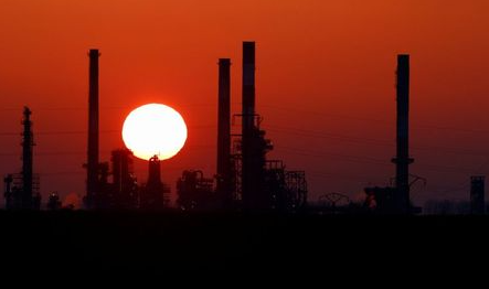 The sun sets behind the chimneys of the Total Grandpuits oil refinery, southeast of Paris, France, March 1, 2021. REUTERS/Christian Hartmann