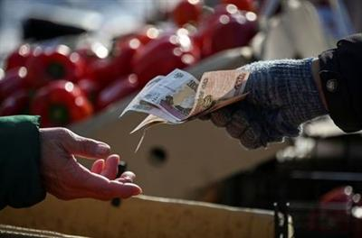 A vendor hands over Russian rouble banknotes to a customer at a street market in Omsk, Russia March 31, 2021. REUTERS/Alexey Malgavko
