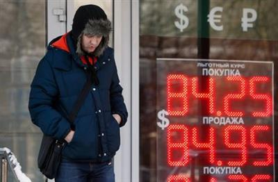 A man walks near a board showing currency exchange rates of the U.S. dollar against the rouble in Moscow, Russia, January 21, 2016. Russia's rouble fell further on January 20, setting a new record low of over 81 roubles per dollar as a bearish mood gripped Russian financial markets. REUTERS/Sergei Karpukhin