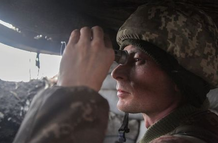 A service member of the Ukrainian armed forces uses binoculars while observing the area at fighting positions on the line of separation near the rebel-controlled city of Donetsk, Ukraine April 3, 2021. REUTERS/Serhiy Takhmazov
