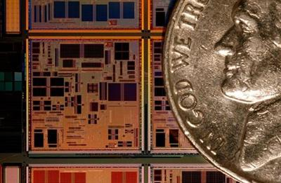 A custom made PowerPC microprocessor seen next to a nickel (a U.S. five cent coin) at the IBM 300 mm Manufacturing Plant in East Fishkill, New York March 24, 2004. This state of the art facility has become one of the largest outsource manufacturers of semiconductors. REUTERS/Chip East CME/JDP