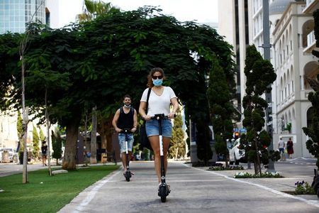 People wearing a protective face mask ride scooters ahead of a nationwide lockdown to contain the spread of the coronavirus disease (COVID-19), which is set to begin on Friday, in Tel Aviv, Israel September 15, 2020. REUTERS/Corinna Kern