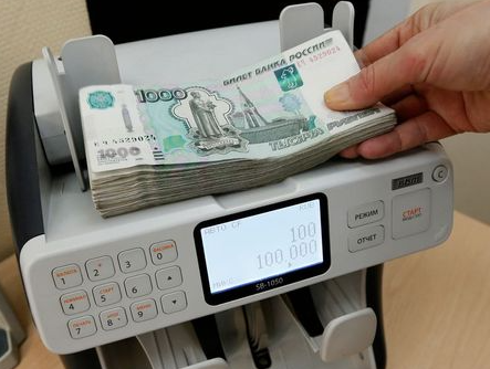 A cashier of a private company, which specializes in the wholesale trade of sweets and confectionery products, uses a machine while counting 1000 rouble banknotes at an office in Krasnoyarsk, Russia, January 22, 2016. The rouble maintained its slide through record lows on January 21, threatening more hardship for ordinary Russians and prompting some to stock up on dollars as the Kremlin denied the currency was collapsing. REUTERS/Ilya Naymushin