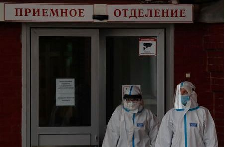 Medical specialists wearing protective gear walk outside a hospital, amid the outbreak of the coronavirus disease (COVID-19) in Saint Petersburg, Russia November 11, 2020. The sign reads: