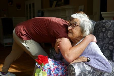 Community coordinator Terence Surin hugs Joan Brock, 101, who is a resident at Alexander House Care Home in Wimbledon, as coronavirus disease (COVID-19) restrictions continue to ease, London, Britain, May 17, 2021. REUTERS/Hannah McKay