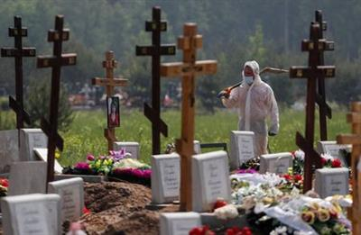 A grave digger wearing personal protective equipment (PPE) walks after burying a person, who presumably died of the coronavirus disease (COVID-19) in the special purpose section of a graveyard on the outskirts of Saint Petersburg, Russia June 10, 2020. REUTERS/Anton Vaganov