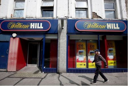 A pedestrian walks past a William Hill betting shop in London, Britain July 25, 2016. REUTERS/Neil Hall