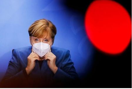 German Chancellor Angela Merkel puts on her face mask at the end of a news conference with Bavarian Prime Minister Markus Soeder and Berlin's mayor Michael Mueller (not pictured) at the Chancellery in Berlin, Germany October 28, 2020. REUTERS/Fabrizio Bensch/Pool TPX IMAGES OF THE DAY