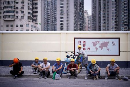 Construction workers rest in a street, following the coronavirus disease (COVID-19) outbreak, in Shanghai, China July 16 2020. REUTERS/Aly Song
