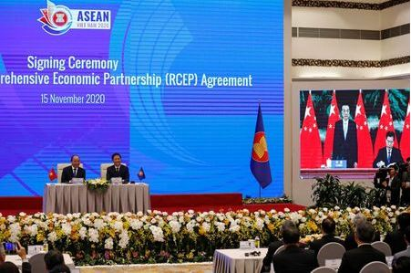 Vietnam's Prime Minister Nguyen Xuan Phuc (L) sits next to Minister of Industry and Trade Tran Tuan Anh as they watch a screen showing Chinese Minister of Commerce Zhong Shan (R) signing next to Chinese Premier Li Keqiang during the virtual signing ceremony of the Regional Comprehensive Economic Partnership (RCEP) Agreement during the 37th ASEAN Summit in Hanoi, Vietnam November 15, 2020. REUTERS/Kham