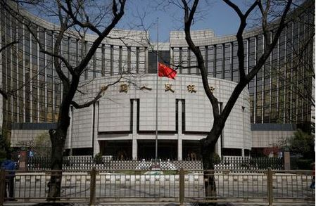The Chinese national flag flies at half-mast at the headquarters of the People's Bank of China, the central bank (PBOC), as China holds a national mourning for those who died of the coronavirus disease (COVID-19), on the Qingming tomb-sweeping festival in Beijing, China April 4, 2020. REUTERS/Carlos Garcia Rawlins