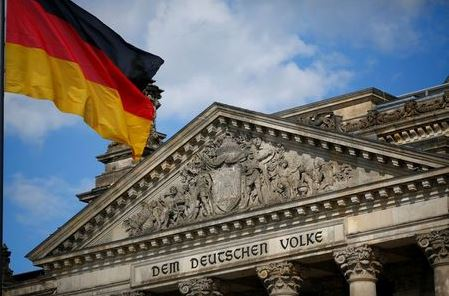 A German flag flutters in front of the Reichstag building in Berlin, Germany, September 6, 2020. Letters read