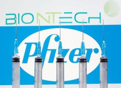 Syringes are seen in front of displayed Biontech and Pfizer logos in this illustration taken November 10, 2020. REUTERS/Dado Ruvic/Illustration