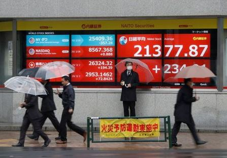 Passersby wearing protective face masks, following an outbreak of the coronavirus, walk past in front of an electric screen displaying Nikkei share average outside a brokerage in Tokyo, Japan March 2, 2020. REUTERS/Issei Kato