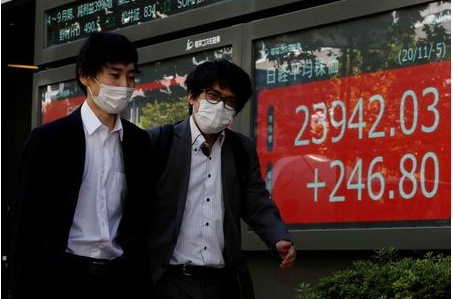 People wearing protective masks, following the coronavirus disease (COVID-19) outbreak, walk past a screen showing Nikkei index outside a brokerage in Tokyo, Japan November 5, 2020. REUTERS/Kim Kyung-Hoon