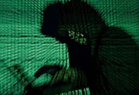 FILE PHOTO: A man holds a laptop computer as cyber code is projected on him in this illustration picture taken on May 13, 2017. REUTERS/Kacper Pempel/Illustration