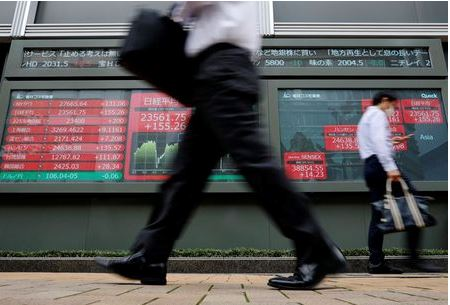 Passersby wearing protective masks walk past an electronic board showing Japan's Nikkei average, the exchange rate between Japanese yen against the U.S. dollar and other world's benchmarks outside a brokerage, amid the coronavirus disease (COVID-19) outbreak, in Tokyo, Japan September 14, 2020. REUTERS/Issei Kato