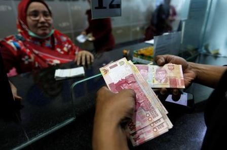 A customer holds Indonesian rupiah bank notes at a money changer in Jakarta, Indonesia August 13, 2018. REUTERS/Willy Kurniawan