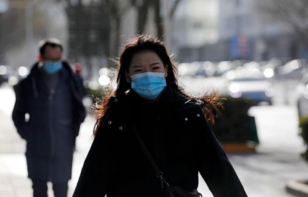 A woman wearing a face mask walks along a street, following new cases of the coronavirus disease (COVID-19) in the country, in Beijing, China January 11, 2021. REUTERS/Tingshu Wang