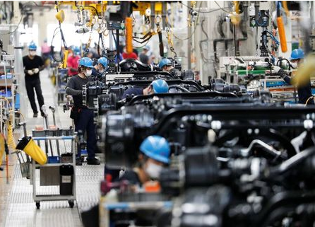 Employees wearing protective face masks work on the automobile assembly line as the maker ramps up car production with new security and health measures as a step to resume fully operation, during the outbreak of the coronavirus disease (COVID-19), at Kawasaki factory of Mitsubishi Fuso Truck and Bus Corp., owned by Germany-based Daimler AG, in Kawasaki, south of Tokyo, Japan May 18, 2020. REUTERS/Issei Kato