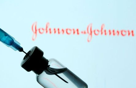 A vial and sryinge are seen in front of a displayed Johnson&Johnson logo in this illustration taken January 11, 2021. REUTERS/Dado Ruvic/Illustration