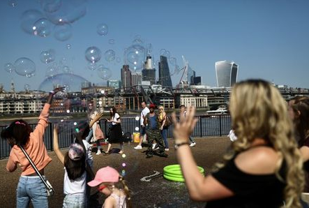 People try to pop bubbles from a street performer on the Southbank in view of London financial district in London, Britain May 7, 2018. REUTERS/Simon Dawson