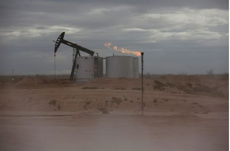 FILE PHOTO: Dust blows around a crude oil pump jack and flare burning excess gas at a drill pad in the Permian Basin in Loving County, Texas, U.S. November 25, 2019. Picture taken November 25, 2019. REUTERS/Angus Mordant/File Photo