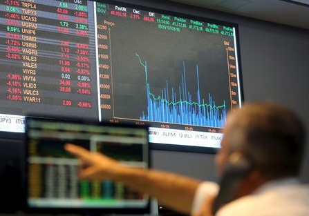 A man points to an electronic board showing the graph of the recent fluctuations of market indices at the floor of Brazil's BM&F Bovespa Stock Market in downtown Sao Paulo, Brazil, January 7, 2016. Latin American currencies weakened on Thursday after China allowed the yuan to drop further, sparking fears of wider economic weakness in the world's top consumer of commodities. REUTERS/Paulo Whitaker