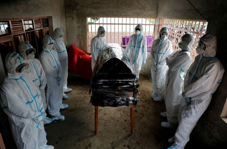 "Men dressed in protective suits stand around the coffin of Kenyan doctor Daniel Alushula who died of complications related to COVID-19, at his funeral, during the coronavirus disease (COVID-19) outbreak, in the village of Khumusalaba, in Kakamega county, Kenya, November 13, 2020. REUTERS/Baz Ratner/File Photo TPX IMAGES OF THE DAY SEARCH ""GLOBAL COVID-19"" FOR THIS STORY. SEARCH ""WIDER IMAGE"" FOR ALL STORIES."