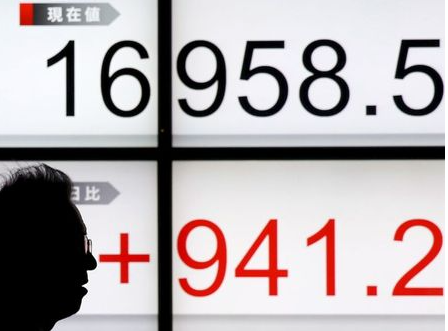 A man walks past an electronic board showing Japan's Nikkei average outside a brokerage in Tokyo, Japan January 22, 2016. Japan's Nikkei share average scored its biggest single-day gain in 4-1/2 months on Friday, helped by a weaker yen, a bounce in oil prices and a hint of more stimulus from ECB president Mario Draghi. REUTERS/Toru Hanai
