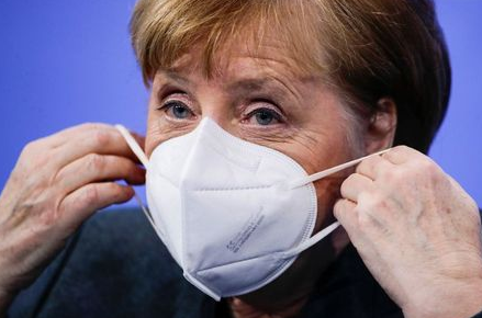 German Chancellor Angela Merkel puts on a face mask after a news conference about further coronavirus disease (COVID-19) measures, at the Chancellery in Berlin, Germany, January 19, 2021. REUTERS/Hannibal Hanschke/Pool