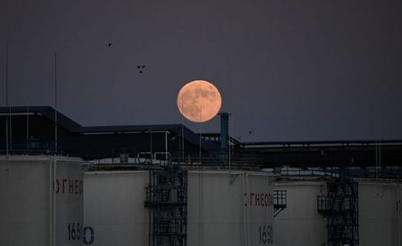 The moon rises behind the storage tanks of a local oil refinery in Omsk, Russia June 5, 2020. Picture taken June 5, 2020. REUTERS/Alexey Malgavko