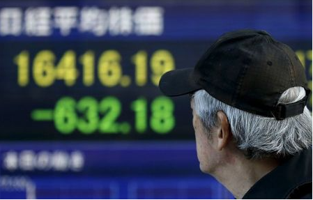 A man walks past an electronic board showing Japan's Nikkei average outside a brokerage in Tokyo, Japan January 20, 2016. Japan's benchmark Nikkei share average tumbled to a fresh 14-1/2 month low on Wednesday as global markets were battered by plunging crude prices that slid to nearly $27 a barrel in the U.S. REUTERS/Toru Hanai