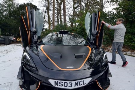 Steve Glynn, who has owned a number of McLarens and says he is willing to try out electric models when they become available, displays his most recently acquired McLaren at his home in Headley Down, Britain February 11, 2021 REUTERS/Nick Carey