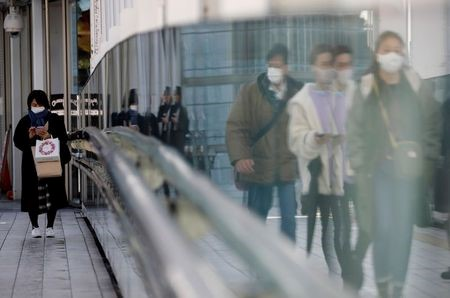 Pedestrians wearing protective masks amid the coronavirus disease (COVID-19) outbreak, make their way in Tokyo, Japan, February 2, 2021. REUTERS/Kim Kyung-Hoon