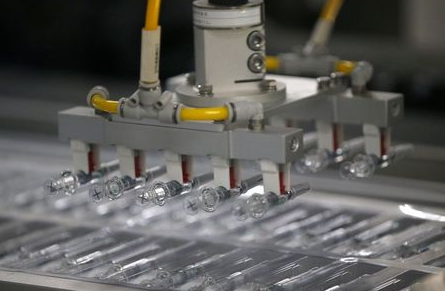 COVID-19 vaccines are seen on a production line inside the Beijing Institute of Biological Products of Sinopharm's China National Biotec Group (CNBG), during a government-organised visit to the company in Beijing, China February 26, 2021. REUTERS/Tingshu Wang
