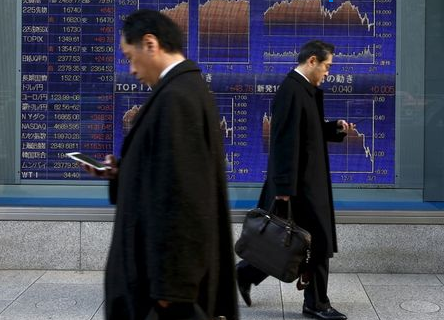 Men walk past an electronic board showing market indices outside a brokerage in Tokyo, Japan, March 2, 2016. Japan's Nikkei surged to a more than three-week high on Wednesday as the dollar rose against the yen after strong U.S. factory and construction data, giving exporters a boost and lifting the overall market. REUTERS/Thomas Peter