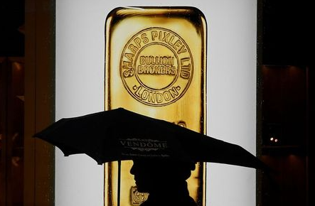 FILE PHOTO: A pedestrian walks past a window displaying a representation of a gold bar at a bullion broker in Piccadilly, London, Britain, December 11, 2017. REUTERS/Toby Melville/File Photo