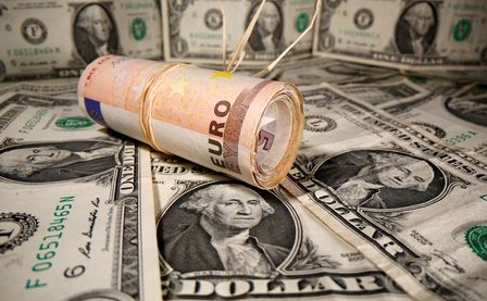 FILE PHOTO: Rolled Euro banknotes are placed on U.S. Dollar banknotes in this illustration taken May 26, 2020. REUTERS/Dado Ruvic/Illustration/File Photo