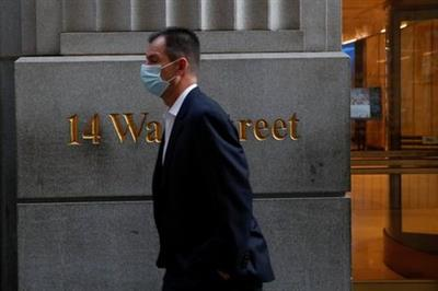 A man wearing a protective face mask walks by 14 Wall Street, as the global outbreak of the coronavirus disease (COVID-19) continues, in the financial district of New York, U.S., November 19, 2020. REUTERS/Shannon Stapleton
