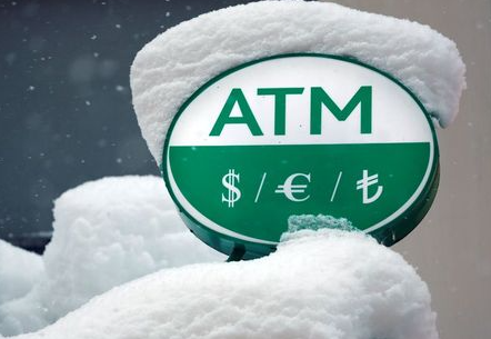 Turkish Lira (TL) and international currency symbols are seen over a snow-covered ATM machine of a bank in central Istanbul, Turkey January 9, 2017. REUTERS/Murad Sezer