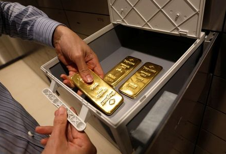 An employee puts gold bullions into a safe deposit box at Degussa shop in Singapore June 16, 2017. Picture taken June 16, 2017. REUTERS/Edgar Su